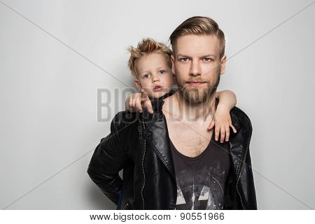 Portrait of young attractive smiling father playing with his little cute son. Fathers day