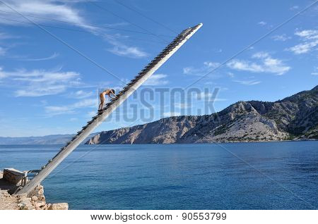 Lifeguard On A Wooden Ladder Above The Sea