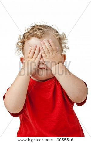 Baby girl covering her eyes with her hands playing peek-a-boo isolated on white