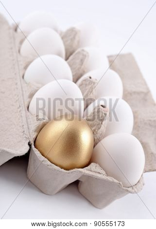 Golden Egg And Jast Eggs In A Cardboard Box On A White