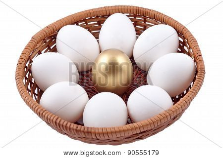 Golden Egg And Jast Eggs In Wicker Bowl On A White