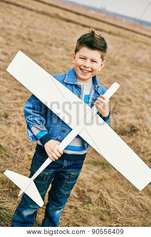 Cheerful kid with toy airplane looking at camera outside