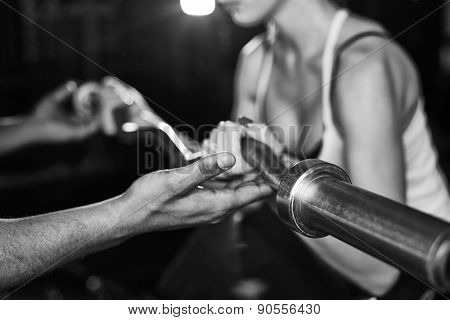 Hand of trainer helping girl lift metal weight