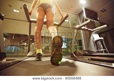 Fit girl running on treadmill in gym