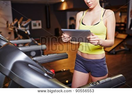 Fit girl in activewear using touchpad while training on sportive equipment