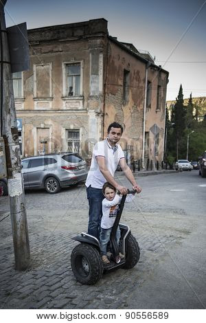 TBILISI, GEORGIA - MAY 02, 2015: A man and his child ride the Segway on the streets of the Old Town