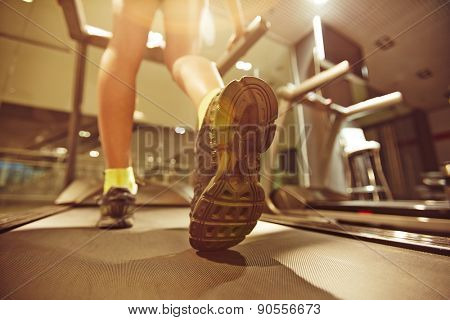 Legs of young woman running on treadmill in gym