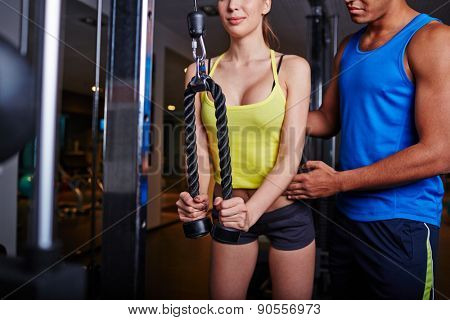 Trainer instructing young woman about exercising on facilities