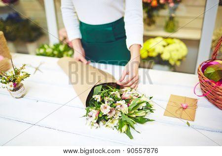 Female florist wrapping up bouquet of white amaryllises