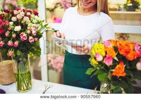 Florist with touchpad standing by workplace