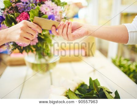 Female florist taking credit card for payment