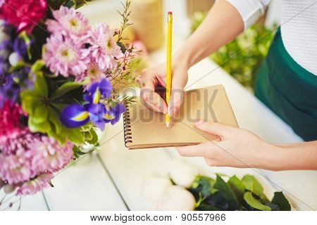 Hands of female florist making notes