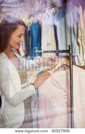 Female choosing new blouse in boutique