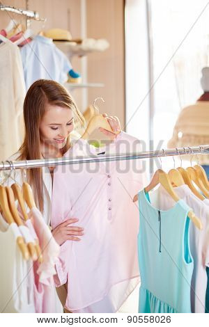 Attractive woman looking for new blouse in clothing department