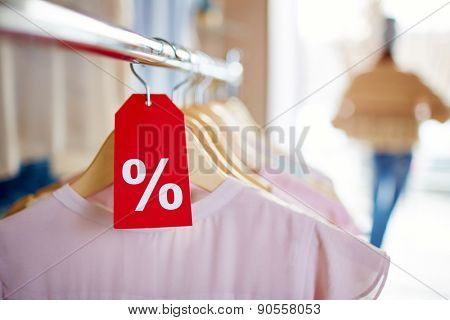 Elegant clothes on hangers with sign of percent on red label