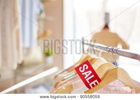 Row of elegant clothes on hangers and label of sale