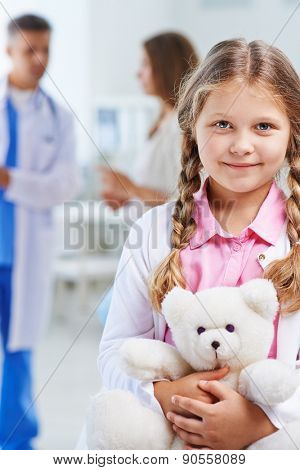 Cute child with white teddy looking at camera while doctor talking to her mother on background