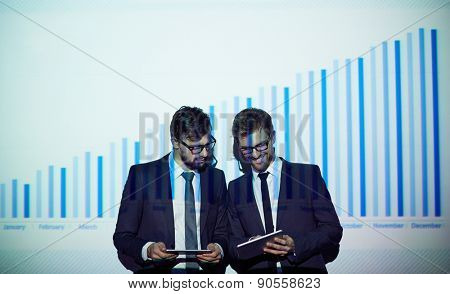 Two colleagues with touchpads networking by chart on the wall
