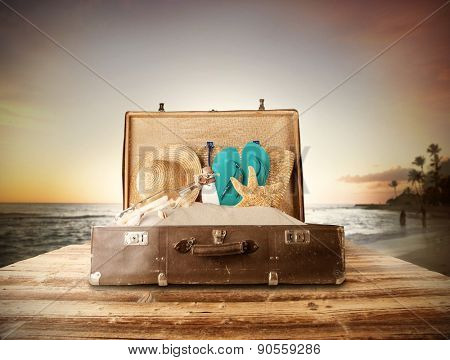 Travel concept with old suitcase on wooden planks full of beach accessories. Placed on mole with sandy beach on background