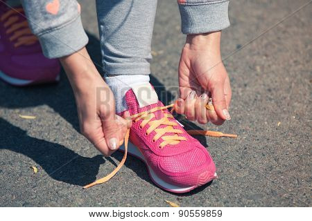 a young girl laces up pink trainers