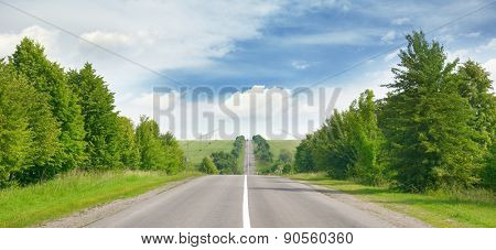 highway among green fields and blue sky