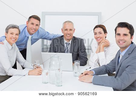 Business team working happily together on laptop in the office