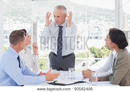 Irritated businessman talking to his team in the office