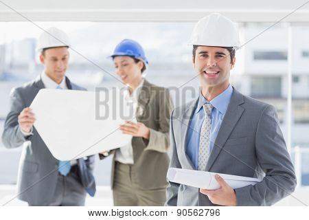 Businessmen and a woman with hard hats and holding blueprint in the office