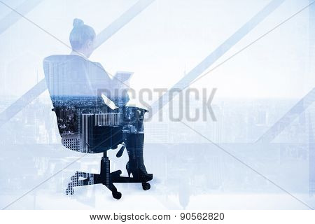 Businesswoman sitting on swivel chair with tablet against high angle view of city skyline