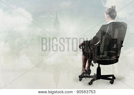 Businesswoman sitting on swivel chair in black suit against new york
