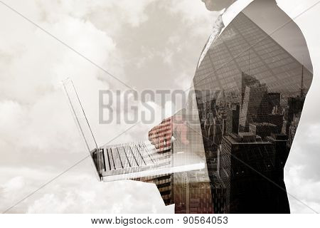 Businessman holding laptop against low angle view of skyscrapers