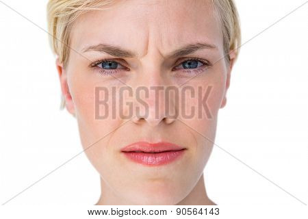 Serious blond woman looking at camera on white background