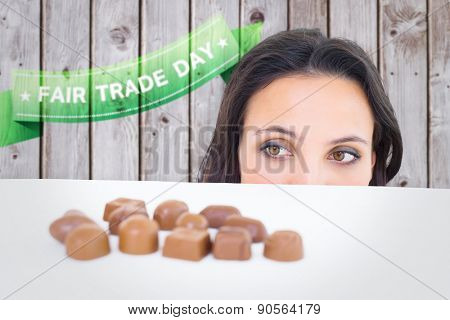 Pretty brunette peeking at chocolate against wooden planks
