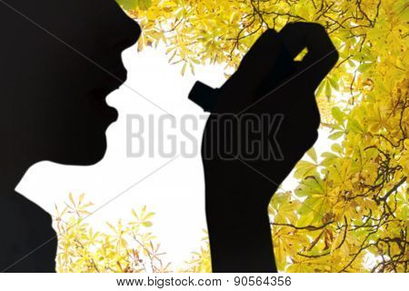 Close up of a woman using an asthma inhaler against autumnal leaves against the clear sky