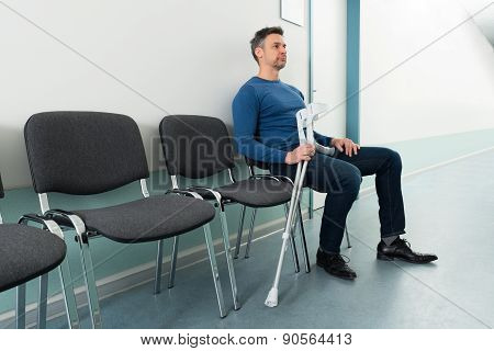 Man Sitting On Chair With Crutches