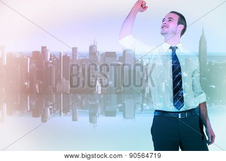Businessman cheering with clenched fist against mirror image of city skyline
