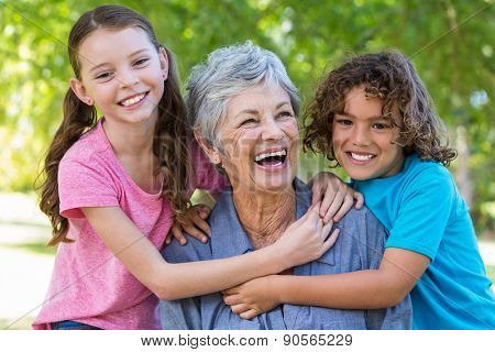 Extended family smiling and kissing in a park on a sunny day