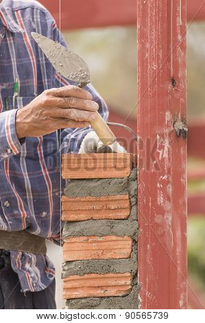 Bricklayer Working In Construction Site Of  Brick Wall