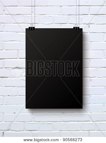 Black blank vertical piece of paper on the white brick wall