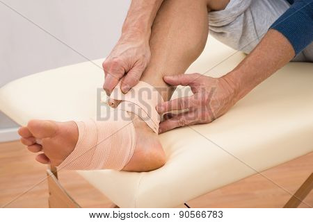 Man Putting Elastic Bandage On Foot