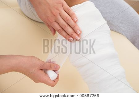 Doctor Bandaging Patient's Leg