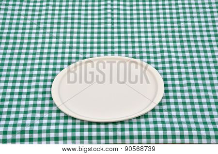 Plate On A Green-white Tablecloth