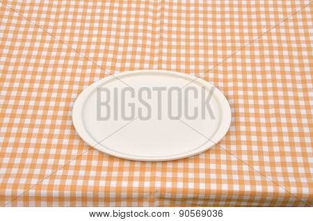 Plate On A Yellow-white Tablecloth