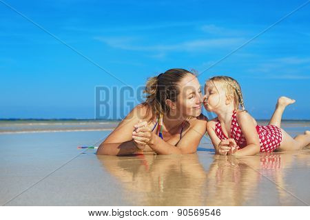 Cute Girl Kissing Happy Smiling Mother On Sea Beach