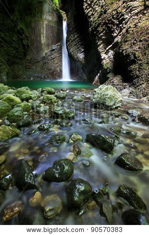 Alpine Spring With Waterfall Falling Into A Narrow Gorge