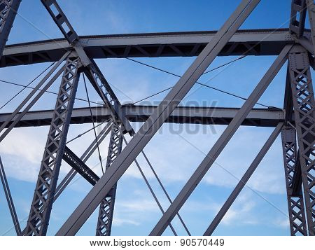 Detail of painted riveted bridge against blue sky.