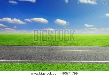 Road And Cloudy Sky And Green Grass