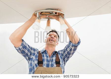 Technician Fixing Light On Ceiling