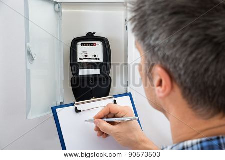 Technician Taking Reading Of Electric Meter