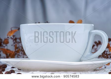 Empty white cup among coffee beans